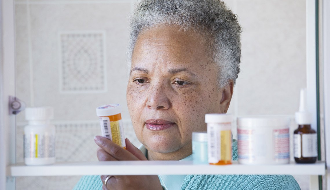 A woman standing in front of a medicine cabinet full of medication and holding a prescription pill bottle