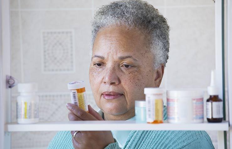 Mujer leyendo las instrucciones de una botella de medicamentos