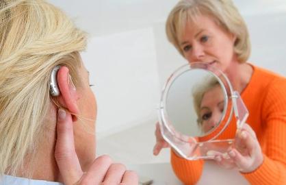Mujer probandose un audífono - Mitos sobre la pérdida auditiva