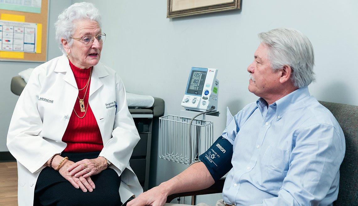 Doctora toma la presión arterial a su paciente