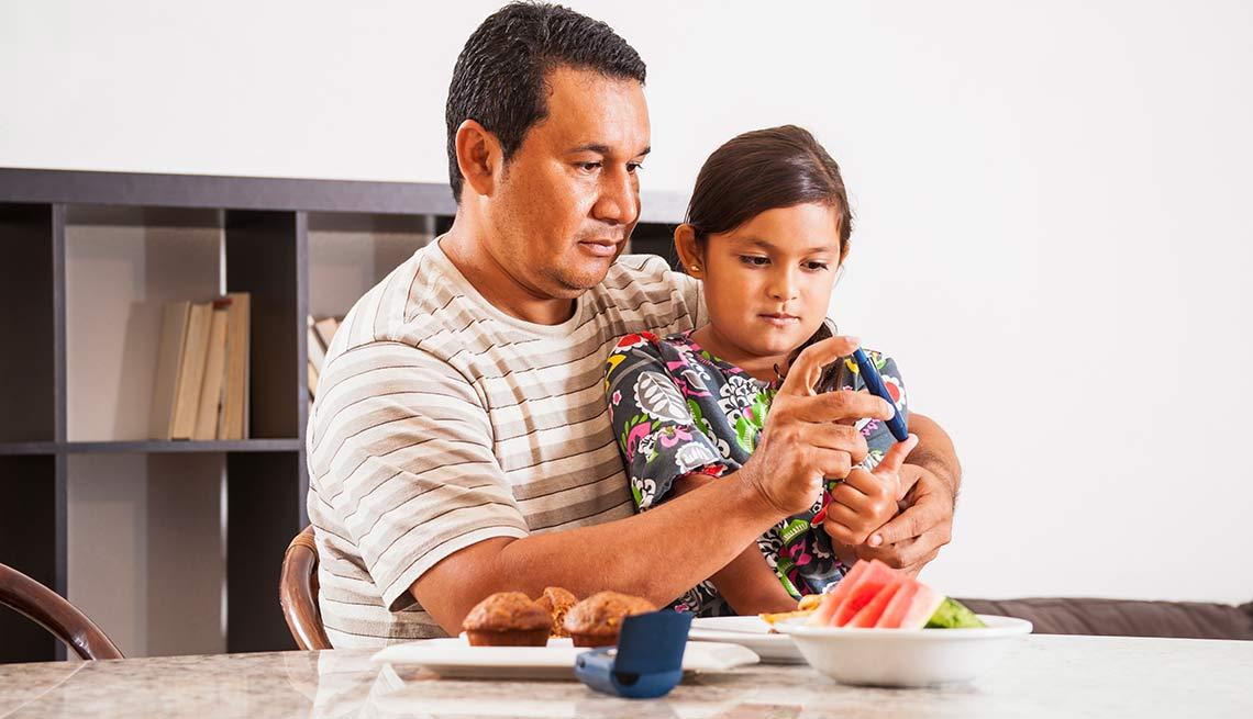Papá tomándo una muestra de sangre a su hija para medir su azúcar