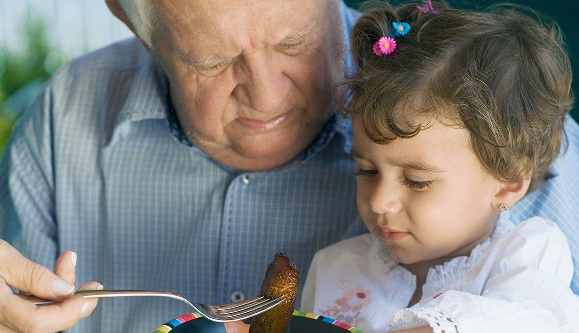 Abuelo dándole de comer a su nieta