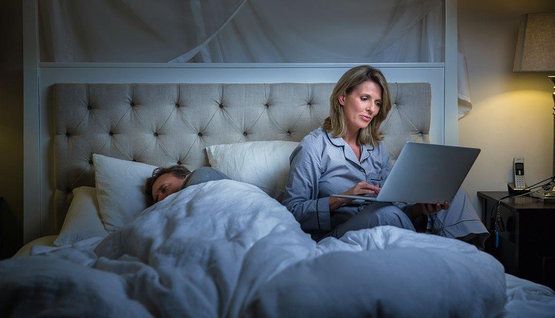 Mujer adulta utilizando un computador en la cama