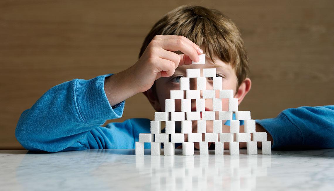 Niño jugando con terrones de azúcar