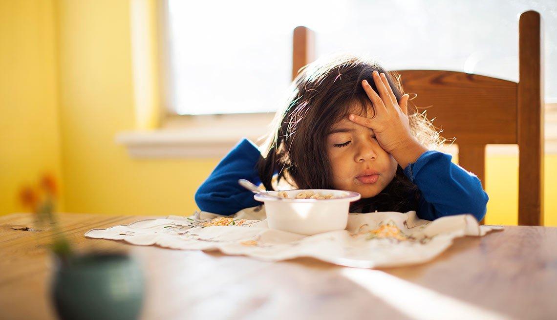 Niña comiendo y somnolienta