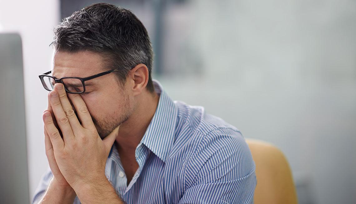 Hombre con sus manos en la cara en señal de agotamiento