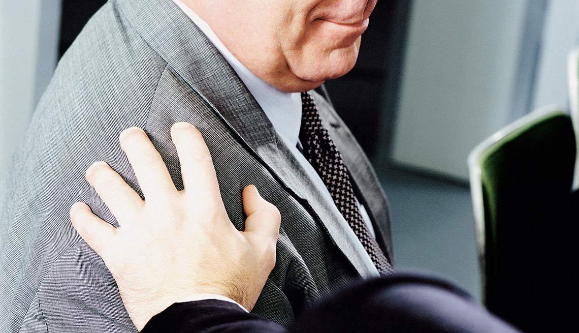 Persona tocando el hombro de otro en señal de compasión