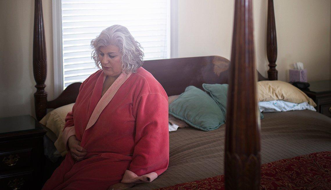 Mujer adulta y obesa sentada sobre una cama