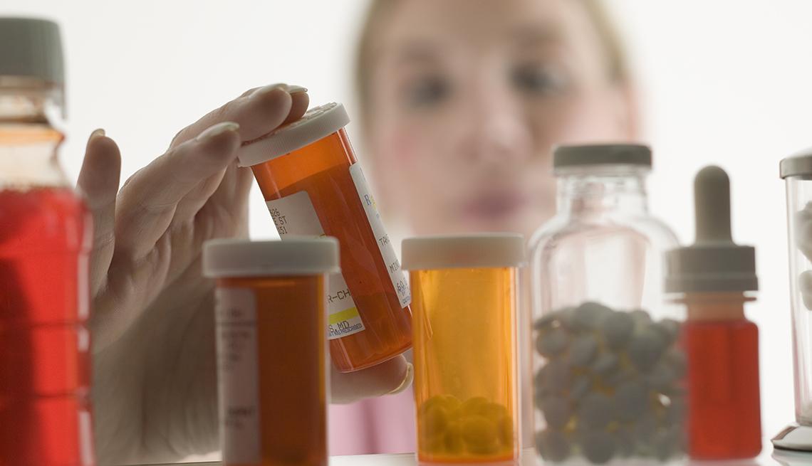Persona buscando entre varios medicamentos