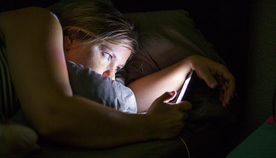 Mujer mirando su celular en la noche