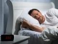 Hombre adulto acostado en su cama sin poder dormir