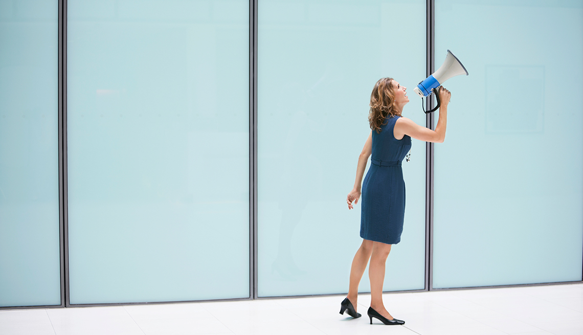 Businesswoman with a megaphone in an office, Workplace hearing loss coping