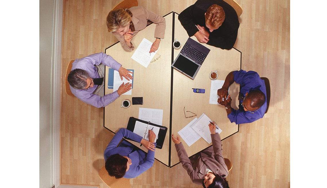 Overhead view of business meeting at a round table, Workplace hearing loss coping stategies
