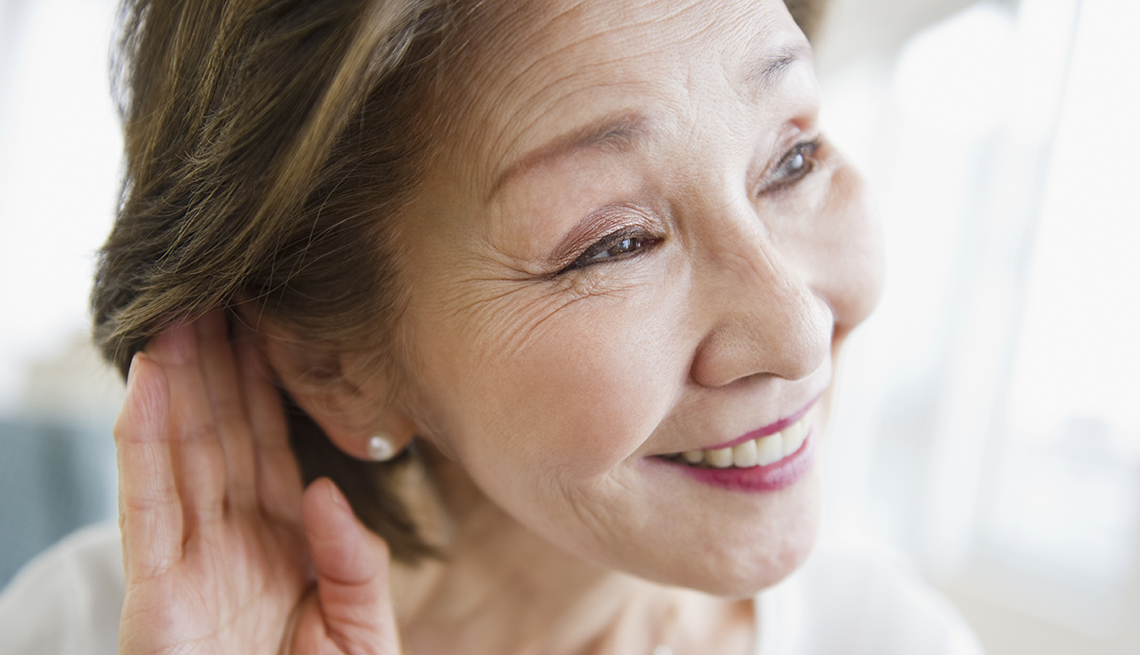 Woman cups her hand behind her ear, Workplace Hearing Loss coping strategies