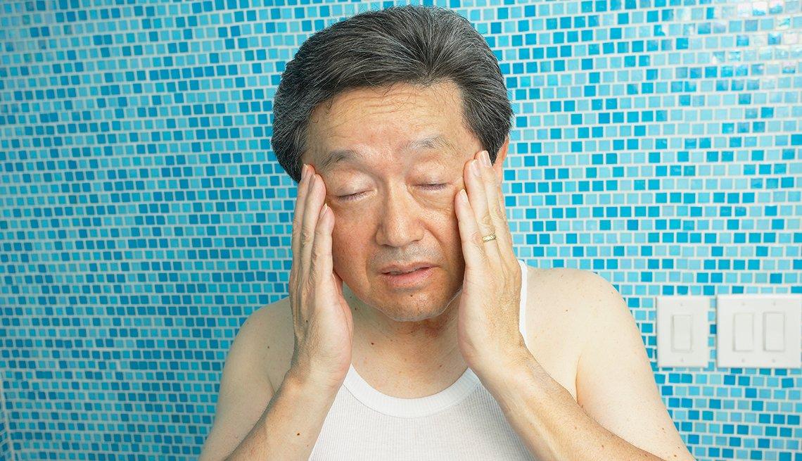 Hombre asiático con sus manos en la cabeza en señal de dolor