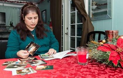 Rosemary Navarro, busca entre viejas fotografías una foto de su madre, Rosa María Navarro, quien también padeció de Alzheimer precoz