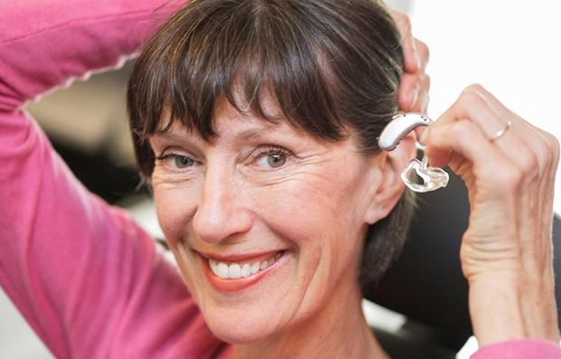 Mujer colocándose un audífono