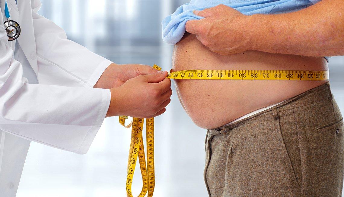 Médico midiendo la cintura de un paciente obeso