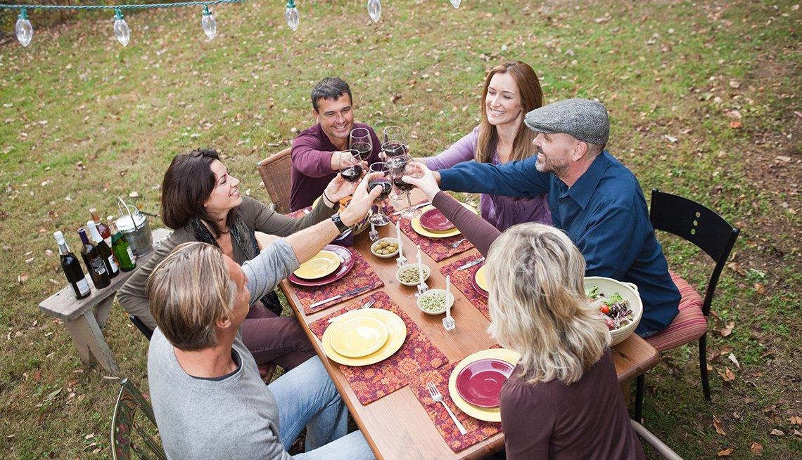 Grupo de amigos celebrando y comiendo en una mesa al aire libre