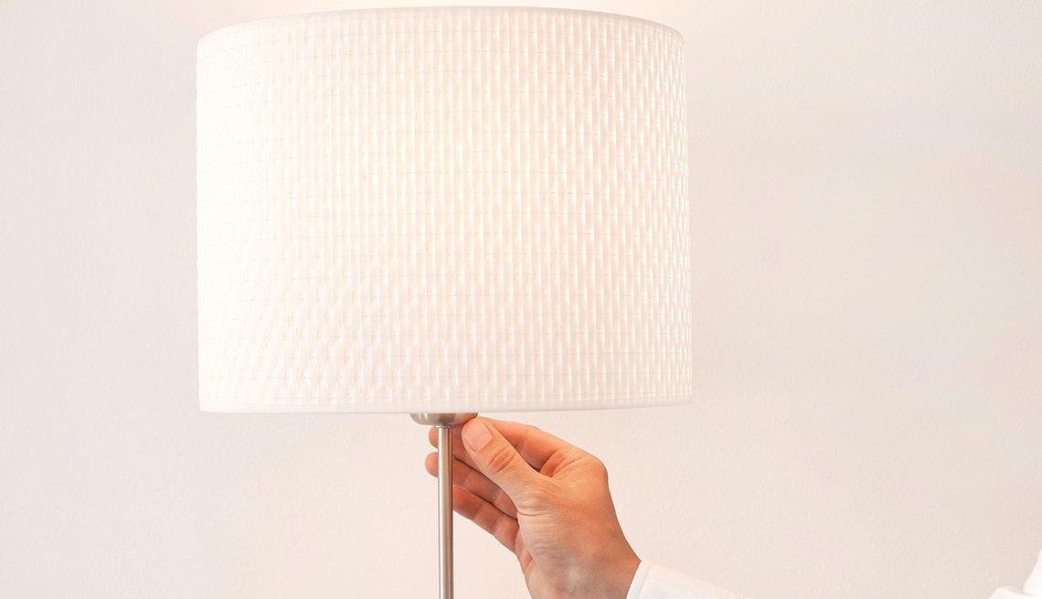 Mano encendiendo una lámpara