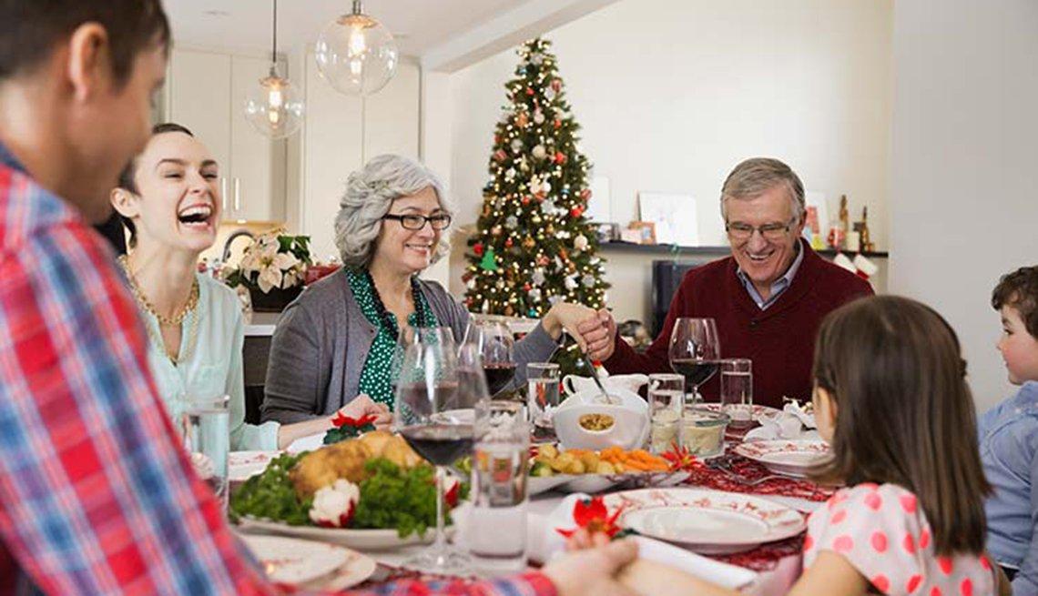 Familia sentada a la mesa celebrando cena de navidad
