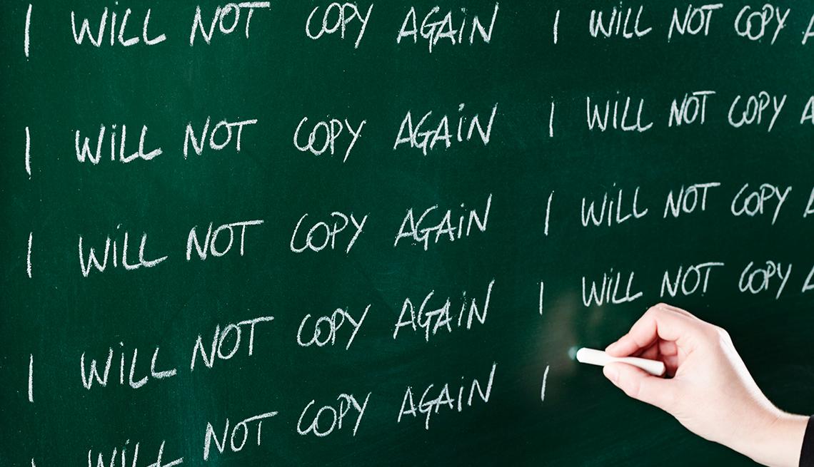 Mano con tiza escribiendo en tablero ´I will not copy again´ (No voy a copiar de nuevo)