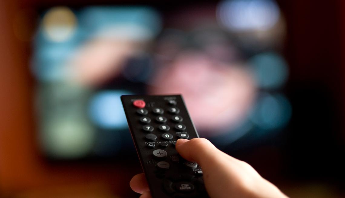 Mano sosteniendo un control remoto en frente de un televisor