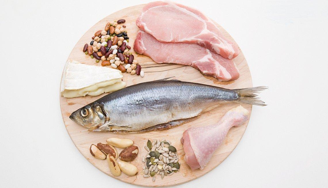 Carnes, pescado, granos y quesos sobre un picador de madera