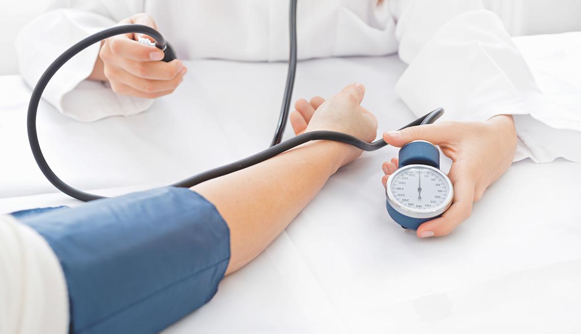 Enfermera tomandole la presión a un paciente