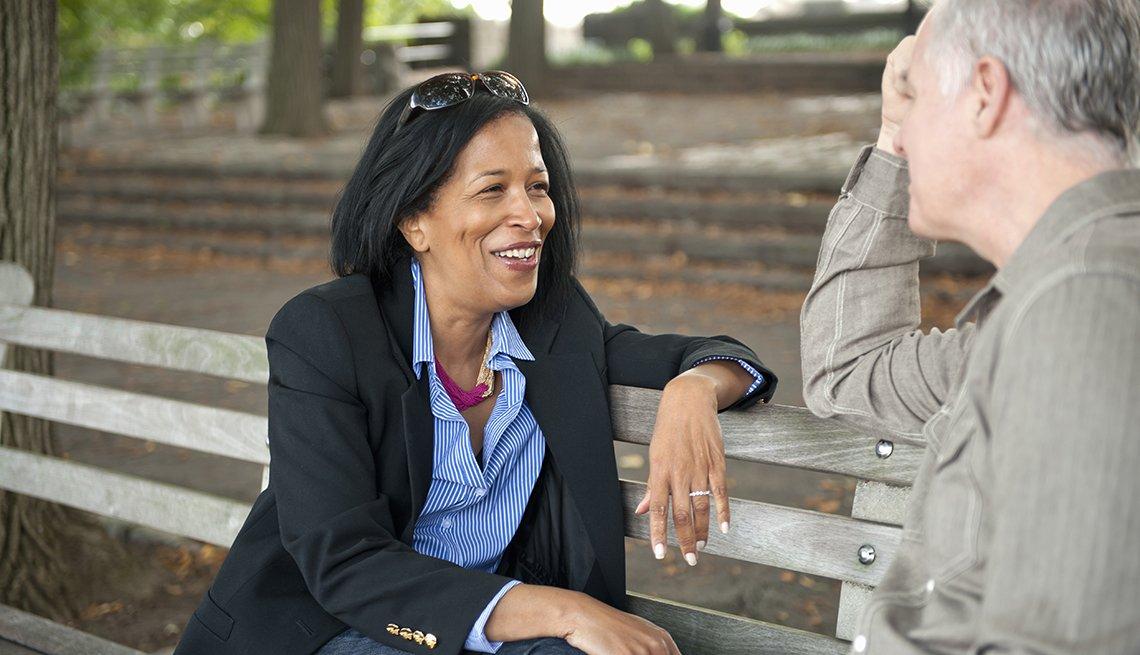 Mujer madura, afro-americana y hombre caucásico maduro hablando en un parque