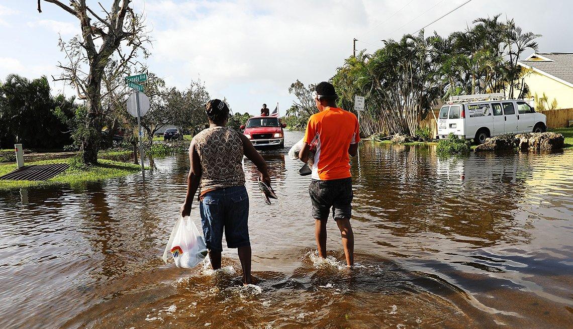 Personas caminando por una zona inundada luego de un desastre natural