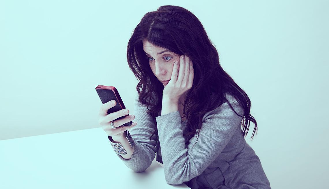 Una mujer mira su celular