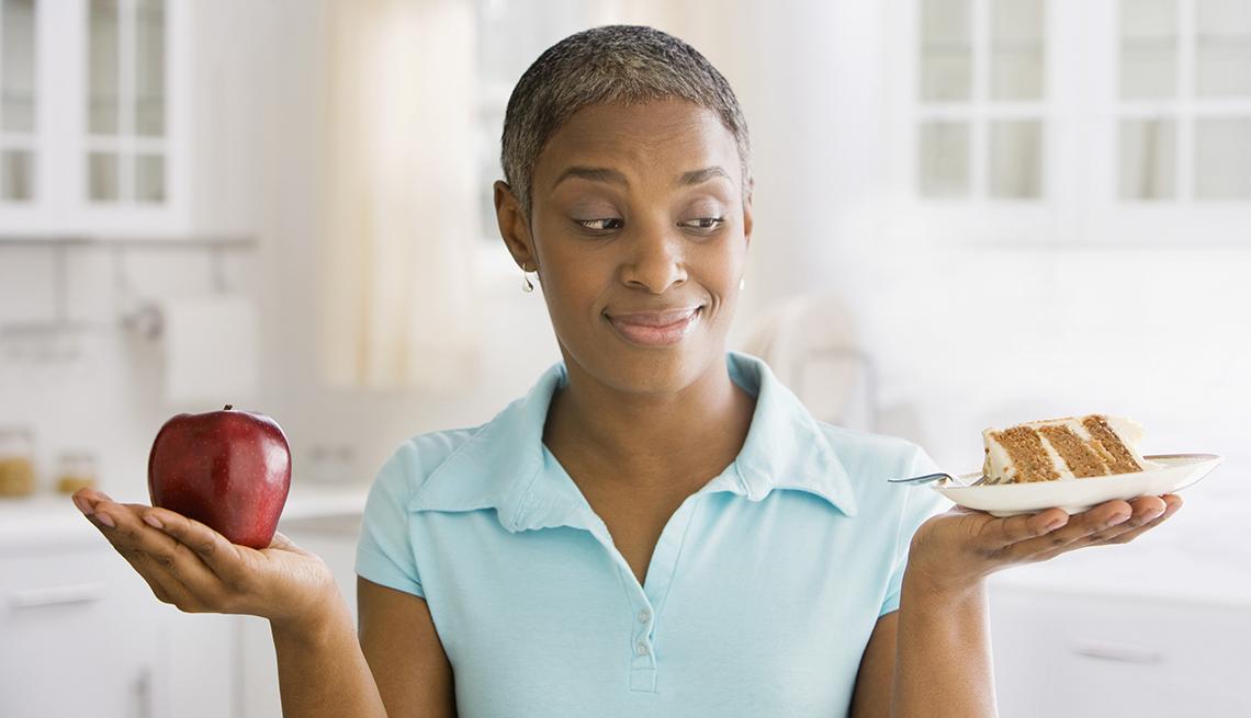 Mujer tratando de decidir entre una manzana y un pedazo de pastel
