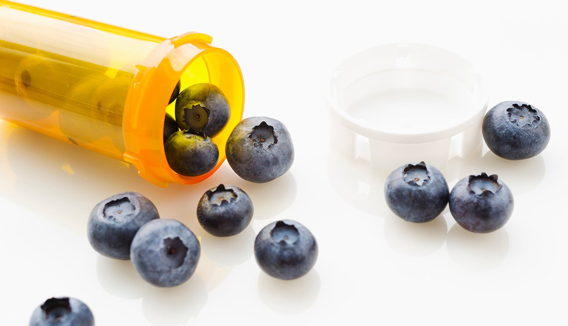 Frasco de medicamentos con arándanos azules