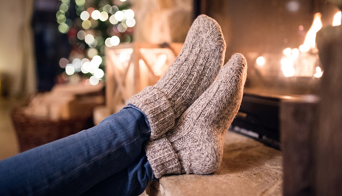 feet crossed with winter socks in front of a fire