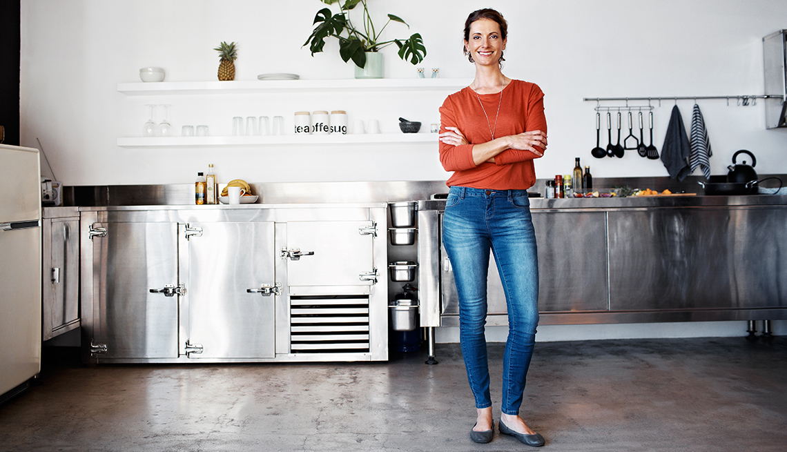 Woman standing with arms crossed in kitchen