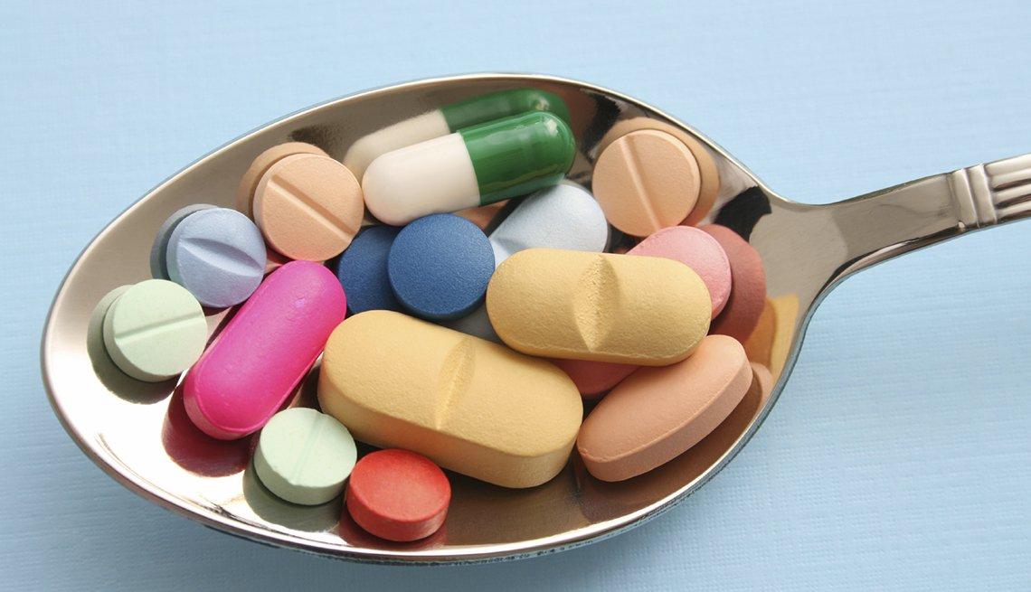 Cuchara llena de medicamentos y vitaminas