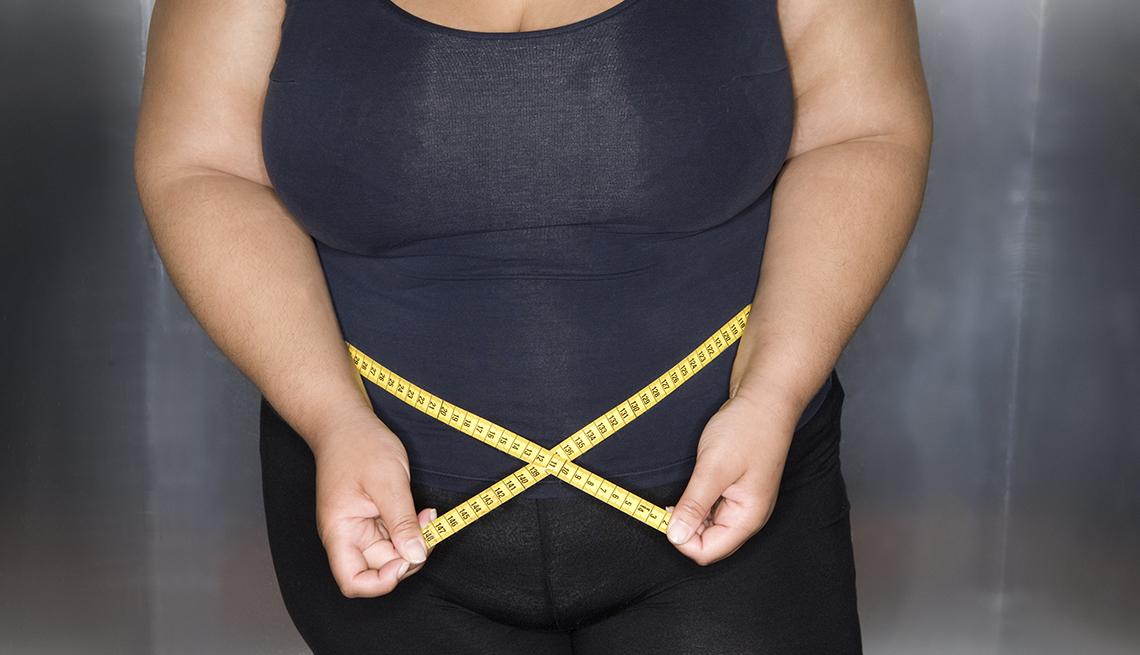 Mujer obesa midiendo su cintura