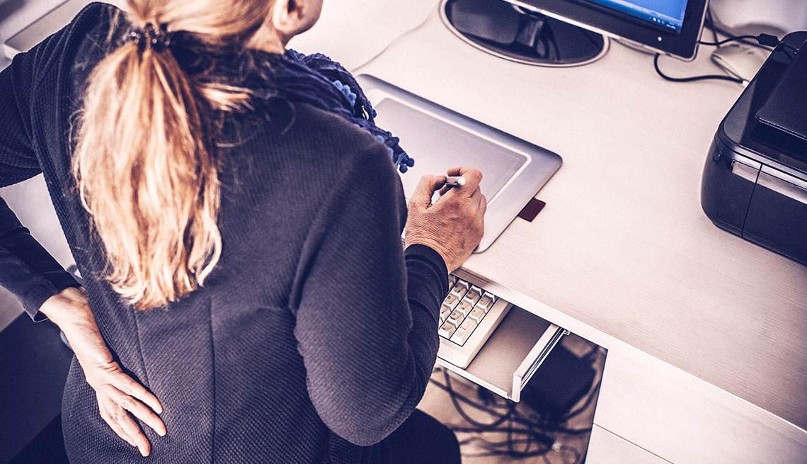 woman with a hand on her lower back in an office setting