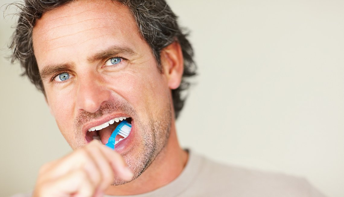 A middle-aged man brushes his teeth