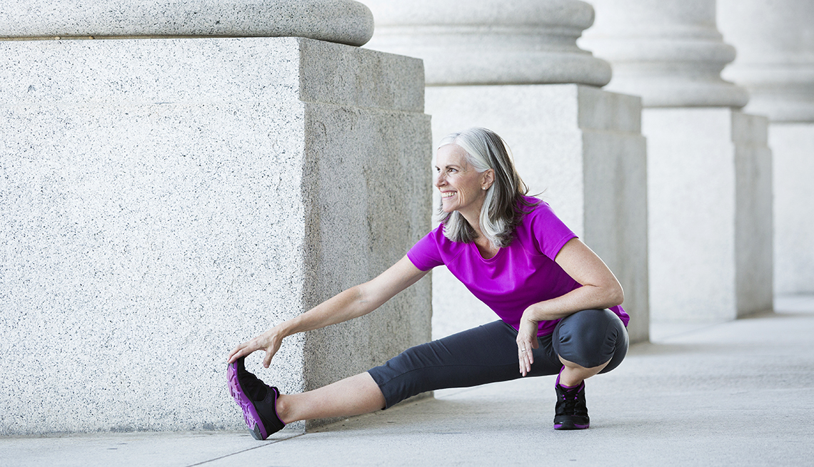woman in exercise clothes stretching outside near large pillars