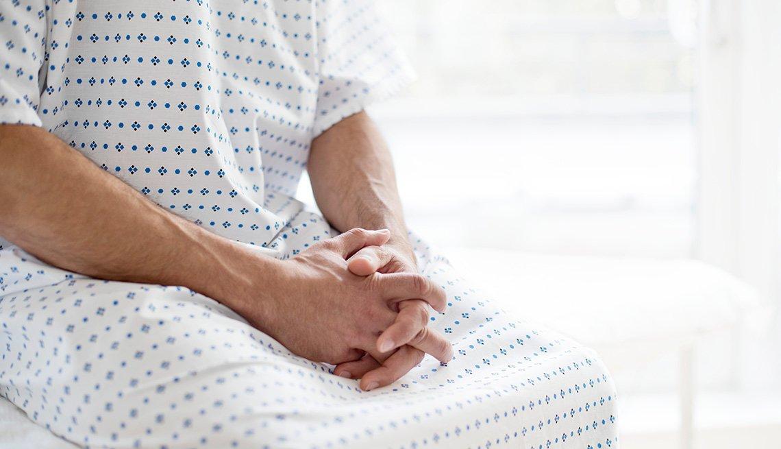 Hombre sentado vestido con una bata de hospital