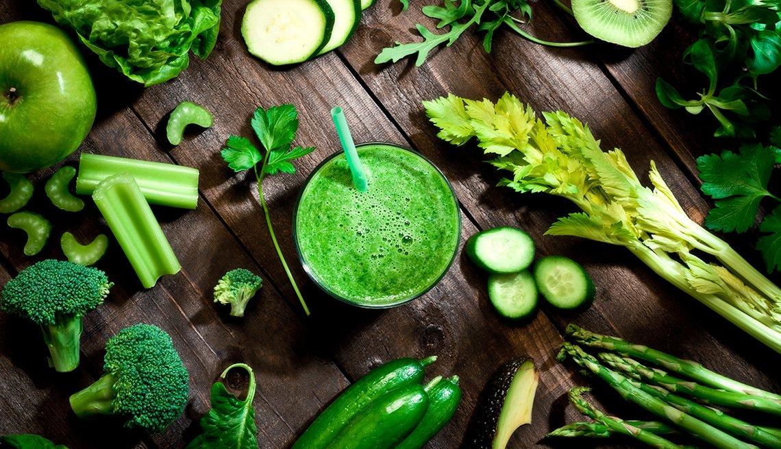 Green veggies surround a green smoothie
