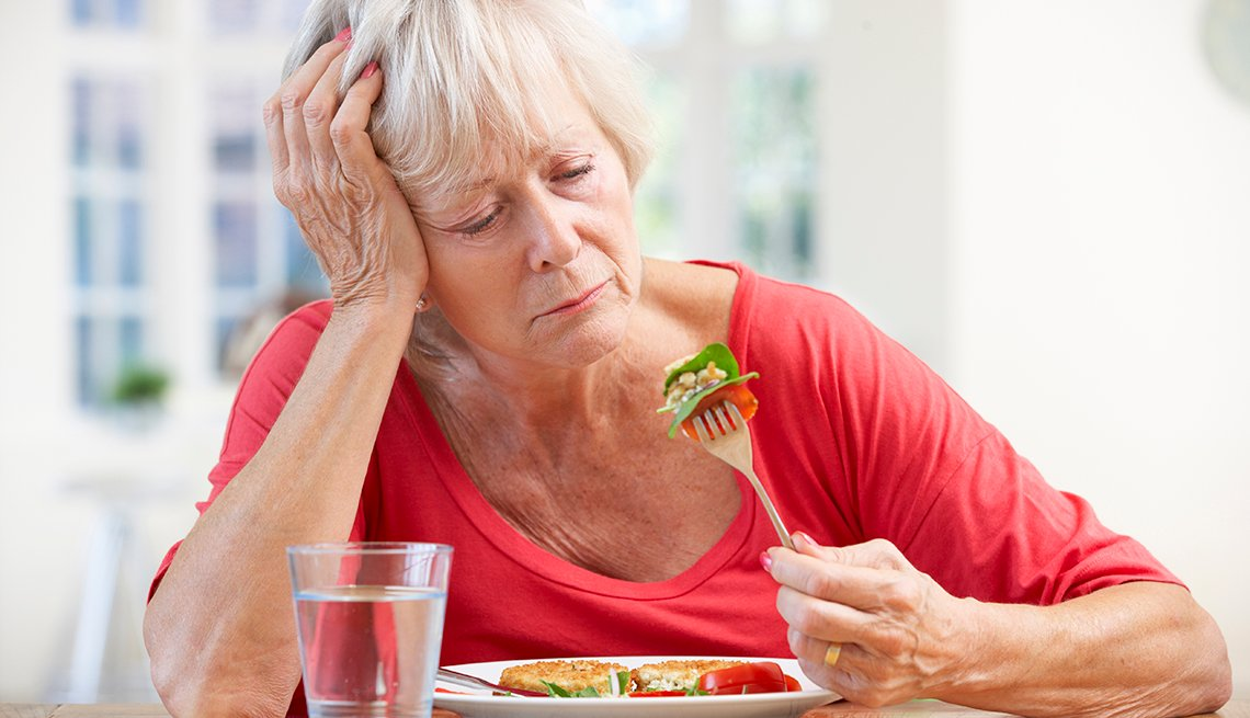 woman looking sadly at bite of food on fork