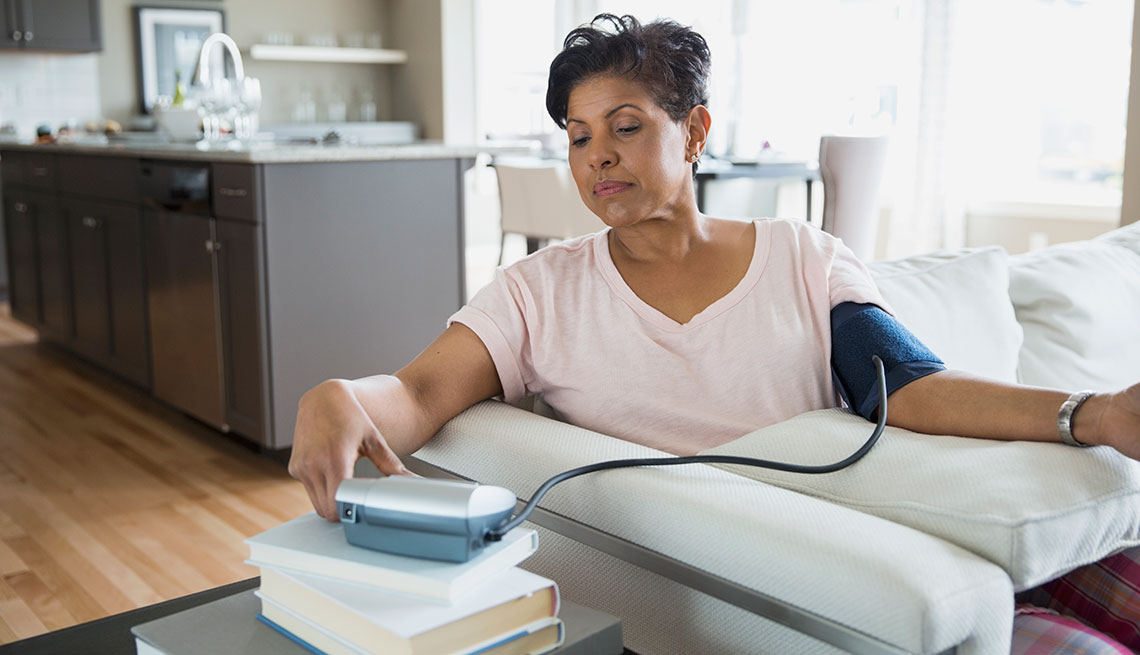 Mature woman measuring her blood pressure at home