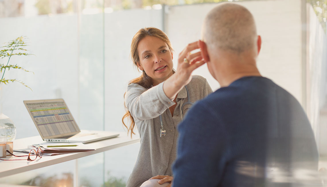 A doctor works with a patient trying out a hearing aid