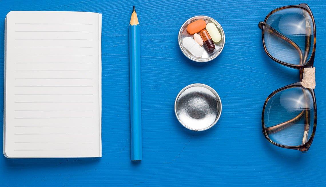 Libreta, lápiz, píldoras y espejuelos sobre un fondo azul