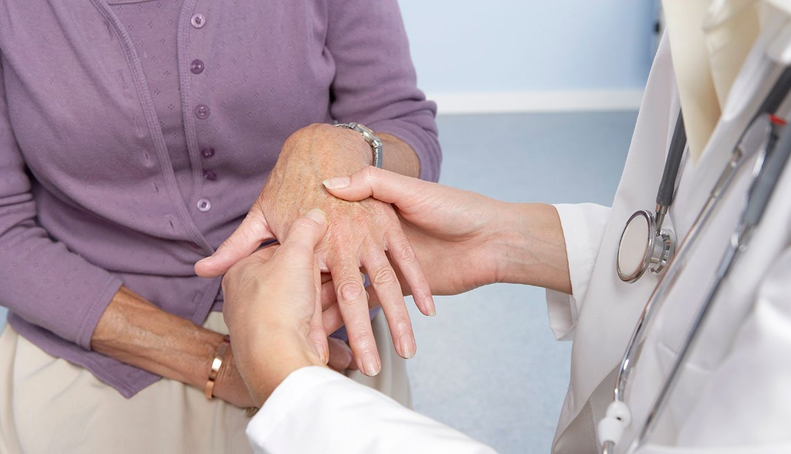 Rheumatoid arthritis. General practitioner examining a patient's hand for signs of rheumatoid arthritis.