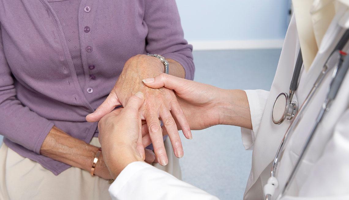 Rheumatoid arthritis. General practitioner examining a patient's hand for signs of rheumatoid arthritis.