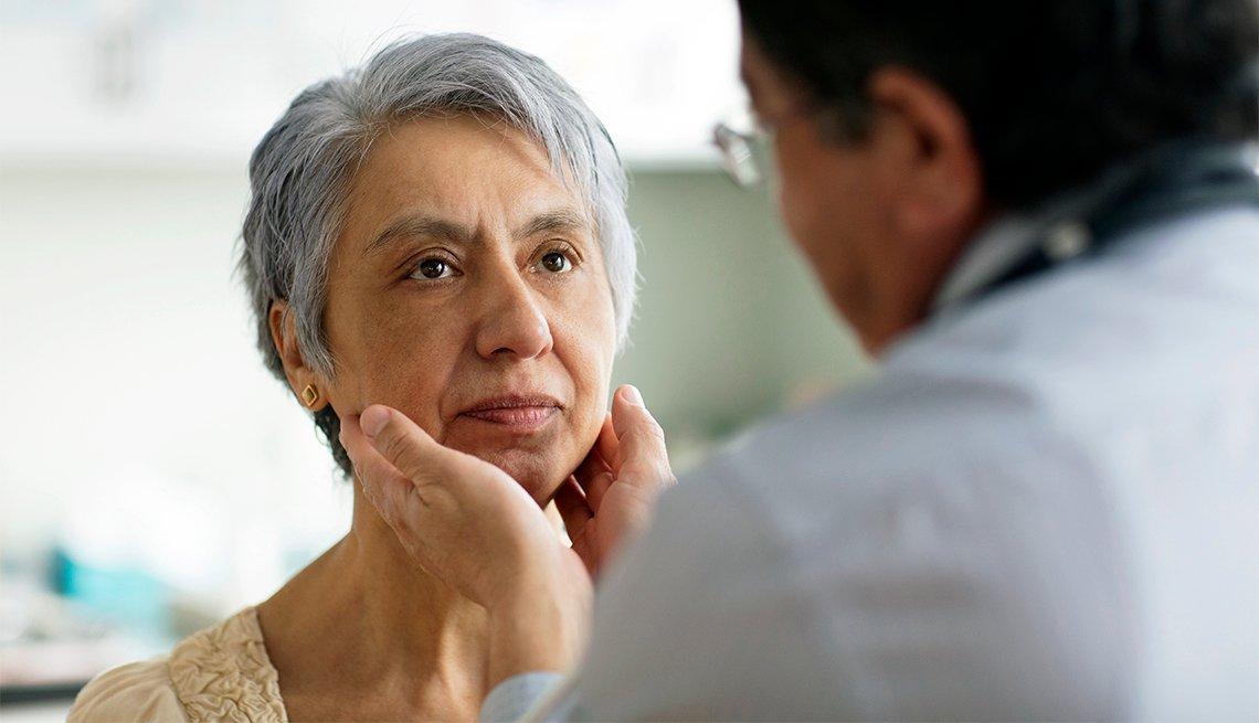 Hispanic doctor examining neck of patient